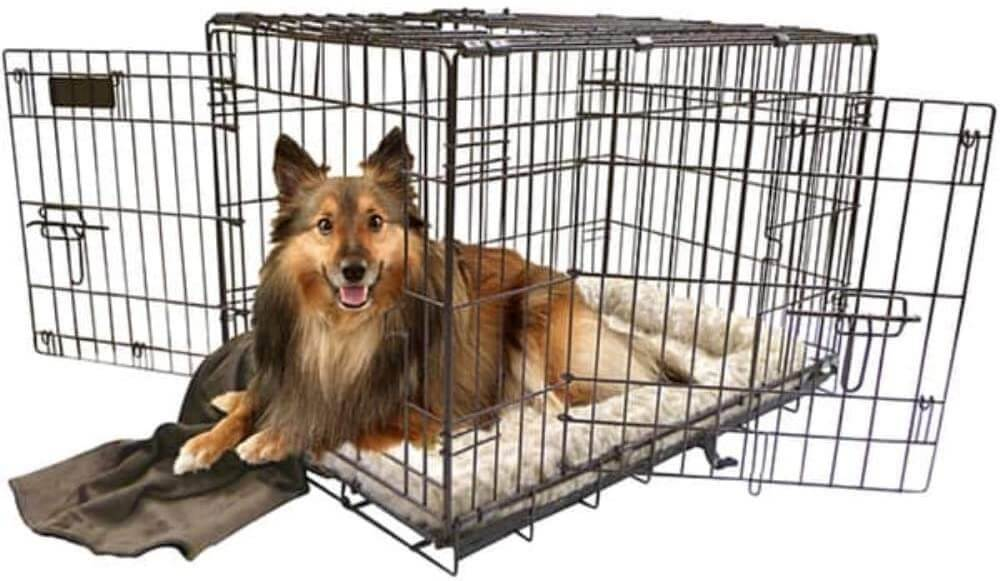 The dog inside a cage resting on its bed and brown blanket